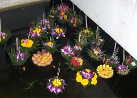 Opferkörbe mit Räucherstäbchen, Kerzen und Münzen